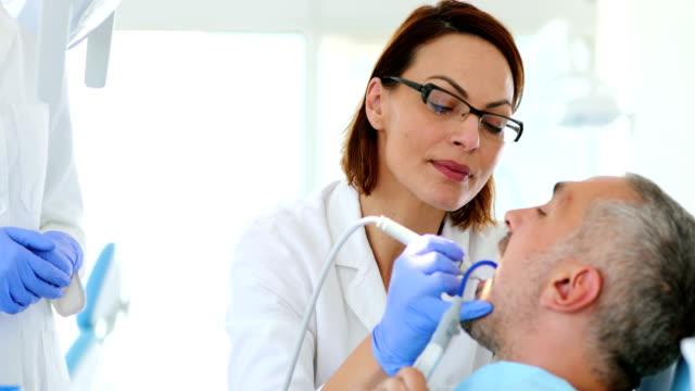 tooth plaque removing procedure. - dentist filmów i materiałów b-roll