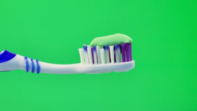 toothbrush and  toothpaste on a green screen.croma key.close-up. - сжимать стоковые видео и кадры b-roll