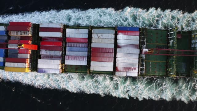 top aerial ascending view of cargo ship from nose to the deck with containers - zoom out stock videos & royalty-free footage