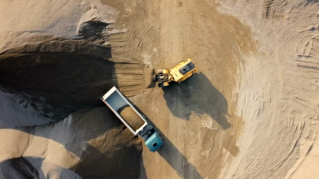 Top aerial time lapse of bulldozer loading stones into empty dump truck in open air quarry. Overhead timelapse of bulldozer in open air quarry construction machinery stock videos & royalty-free footage