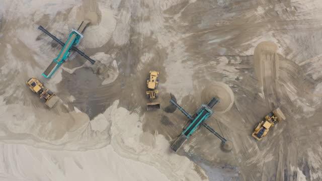 top flyg bild av bulldozer lastning sand i tomma dumper i utomhus stenbrott. - excavator bildbanksvideor och videomaterial från bakom kulisserna