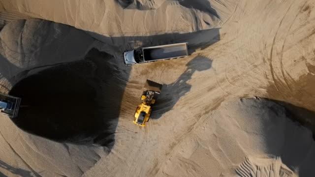 top-luftaufnahme von planierraupen, die steine in einen leeren muldenkipper im freiluftsteinbruch laden. - aerial overview soil stock-videos und b-roll-filmmaterial