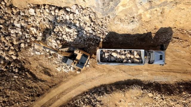 vídeos y material grabado en eventos de stock de vista aérea superior de las piedras del cargamento del excavador en el volquete en mina al aire libre. - pesado