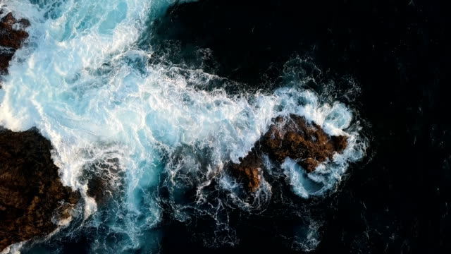 stockvideo's en b-roll-footage met top luchtfoto van ocean waves splash against rocks achtergrond, tenerife, canarische eilanden, spanje. - rocks sea