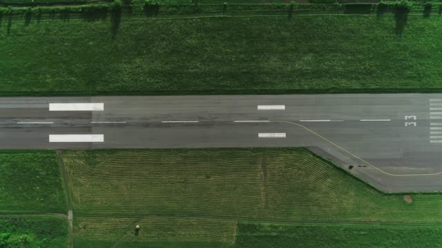 Top aerial view of take off runaway with bright painted lines on it. 4K. Aerial view of airfield of flying club with take off ruaway. Copy space. airfield stock videos & royalty-free footage