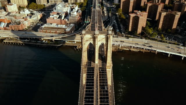 Top aerial view of the Brooklyn bridge through the East river to Manhattan in New York, America. Flag waving on the wind video