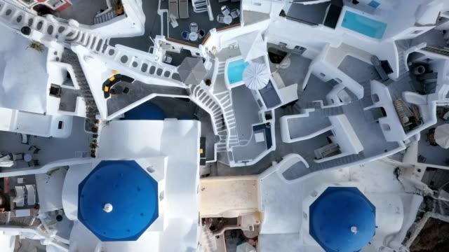 vídeos y material grabado en eventos de stock de superior vista aérea de la iglesia de tres cúpulas azules en la ciudad de oia en la isla de santorini, grecia - grecia europa del sur