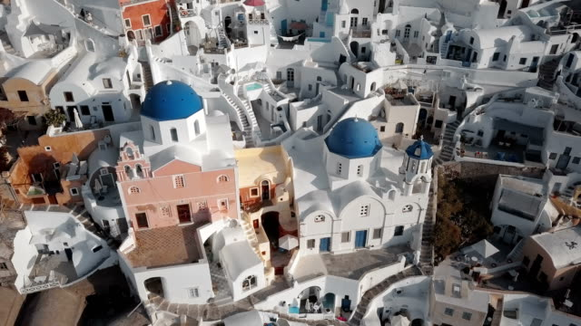 Top aerial view of Three Blue Domes church in Oia town on Santorini island, Greece