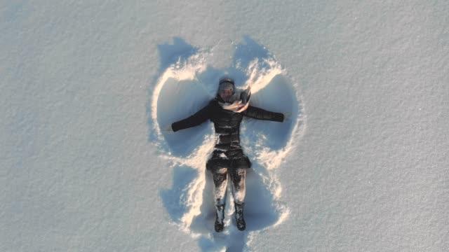 vídeos y material grabado en eventos de stock de superior vista aérea de feliz sonriente joven haciendo la figura de ángel de nieve brazos y acostado en la nieve, actividad al aire libre del invierno - acostado