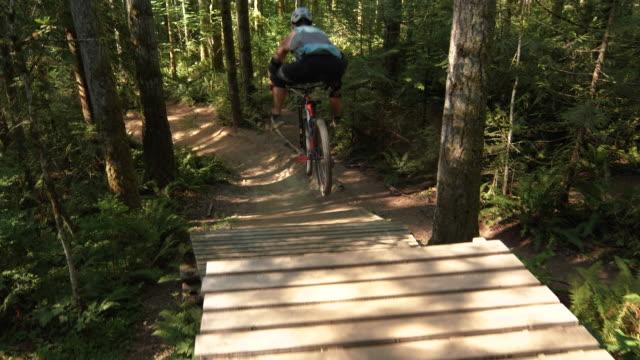 ウッドジャンプから足のないマウンテンバイクの空気のために足を広げる男のトップアングル ビデオ