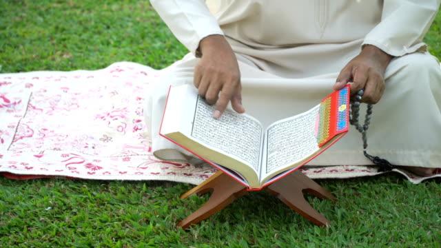 stockvideo's en b-roll-footage met top hoekmening: moslim grootvader lezen quran in openbaar park - koran