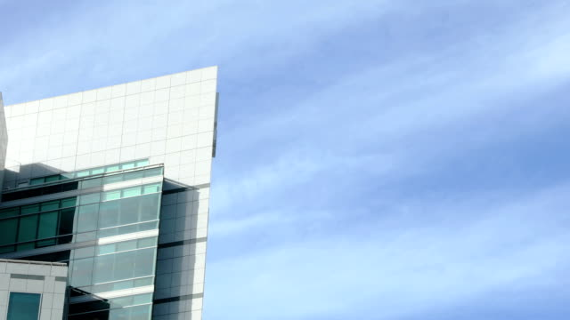 Top corner of office building with sky on sunny day 4k video handheld Top corner of office building with sky on sunny day 4k video handheld office park stock videos & royalty-free footage
