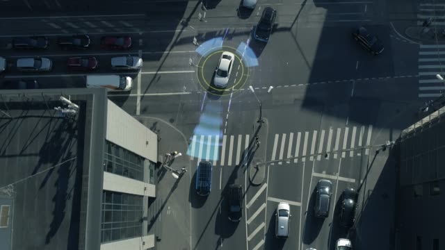 Top Down Aerial Drone: White Autonomous Self Driving Car Moving Through City. Concept: Artificial Intelligence Scans Surrounding Environment, Detecting Cars, Avoids Traffic Jams and Drives Safely.