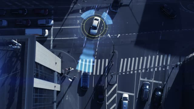 Video Top Down Aerial Drone: White Autonomous Self Driving Car Moving Through City. Concept: Artificial Intelligence Scans Surrounding Environment, Detecting Cars, Avoids Traffic Jams and Drives Safely.