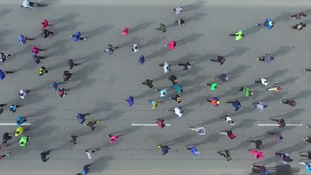 vídeos de stock, filmes e b-roll de parte superior para baixo tiro aéreo de corredores de maratona na estrada asfaltada - fazendo cooper