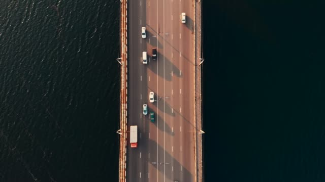 Top down aerial view of car traffic on bridge over river, drone shot video