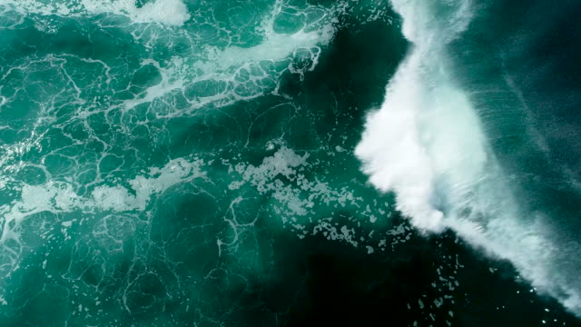 Top down aerial view of giant ocean waves crashing on sunny day Top down aerial birds eye view looking straight down of giant abstract ocean waves breaking in 4k giant fictional character stock videos & royalty-free footage