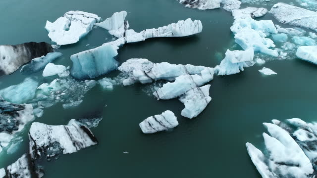 vídeos de stock e filmes b-roll de top down aerial view of glacier icebergs floating in lagoon in iceland - iceberg