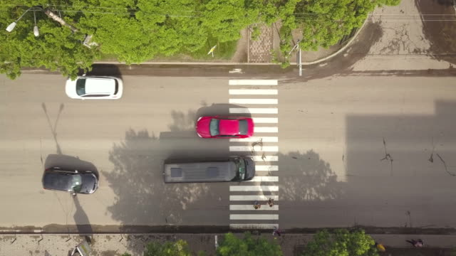 Top down aerial view of street with moving cars and zebra crosswalk with crossing pedestrians.