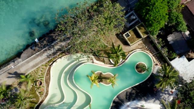 vídeos de stock e filmes b-roll de top down aerial view of villa with swimming pool at toya pakeh harbour at nusa penida island, bali - indonesia - bali
