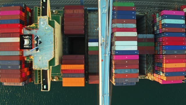 Top Down Drone Flight Over Crane Booms Extended Over Container Ship