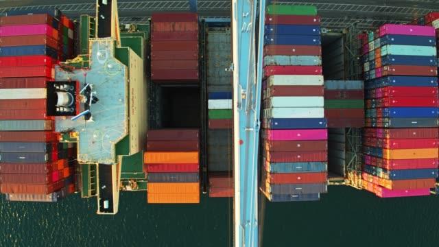 Top Down drone vol sur grue booms étendu sur le navire à conteneurs - Vidéo