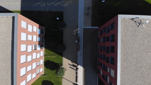 Top down drone shot of a business or university campus with people walking from building to building.
