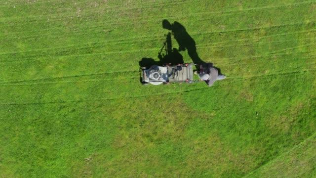 top-down drone skott av mannen gräsklippning i bakgård - gräsmatta odlad mark bildbanksvideor och videomaterial från bakom kulisserna