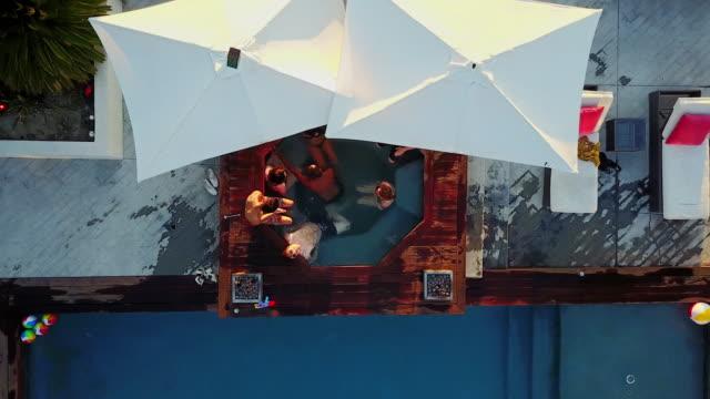 Arriba abajo tiro de Drone de personas colgando hacia fuera en una bañera de hidromasaje - vídeo