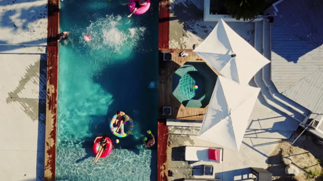 Top Down Drone Shot of People Playing Around in a Backyard Swimming Pool Top down drone shot flying across a backyard where a group of people are playing around and floating on inflatables. pool party stock videos & royalty-free footage