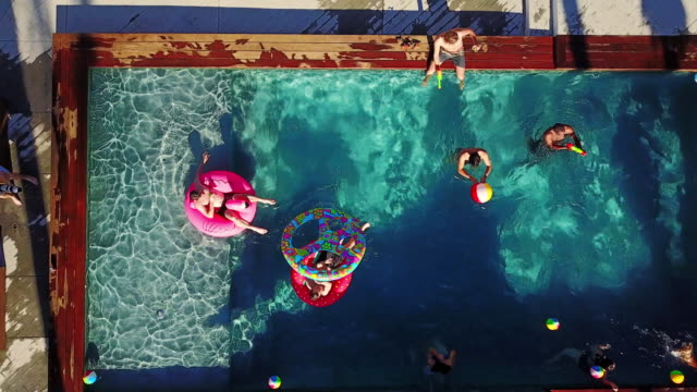 Top Down Drone Shot of People Playing Around in a Backyard Swimming Pool video