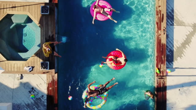top down drone shot of people playing around in a backyard swimming pool - vacanze video stock e b–roll