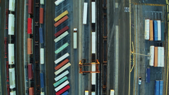 トップダウンの広大な出荷ヤードでコンテナー、トレーラー トラックを配送の行のドローン ショット - トラック点の映像素材/bロール