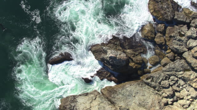 top down drone shot of swirling waves around cliffs in big sur - cliffs stock videos & royalty-free footage