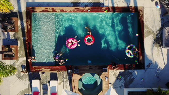 Top Down Drone Shot Pulling Up from People Playing Around in a Backyard Swimming Pool video