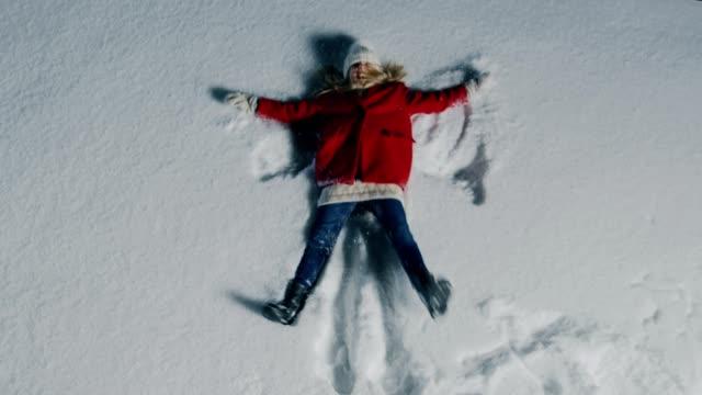 top-down bilder av den glada söt lilla flickan faller i snö, liggande och göra snöängel. barn njuta av vintervädret. - snow kids bildbanksvideor och videomaterial från bakom kulisserna