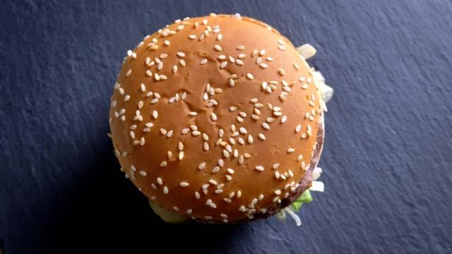 운동으로 회전 하는 빵에 참 깨와 함께 식욕을 돋 우는 더블 치즈 버거의 하향식 촬영. - burger and chicken 스톡 비디오 및 b-롤 화면