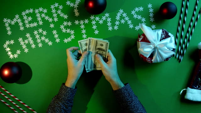 Top down shot of adult man counting cash by Christmas table with chroma key video