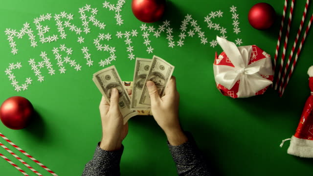 Top down shot of adult man counting cash money and putting them into Christmas gift box on table with chroma key video