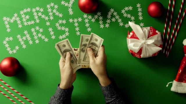 成人男性の現金を数えるとクロマ キーを持つテーブルのクリスマス ギフト ボックスに入れてのショット トップダウン ビデオ