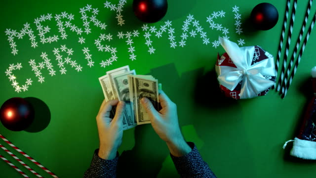 Top down shot of adult man counting cash money and putting them into New Year gift box on table with chroma key video