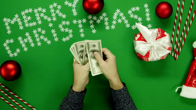 Top down shot of adult man counting cash money and putting them into Xmas gift box on table with chroma key video