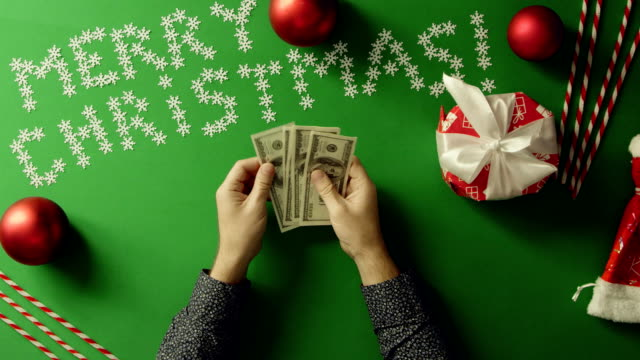 Top down shot of adult man counting cash money by Christmas table with chroma key video