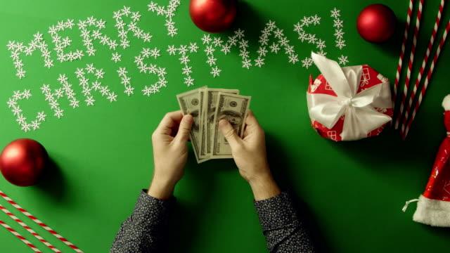 上下にクロマキーでクリスマス テーブルで現金を数える成人男性のショット ビデオ