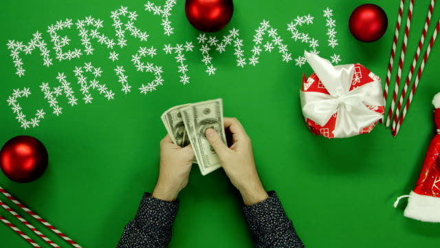 Top down shot of adult man counting money by Christmas table with chroma key video