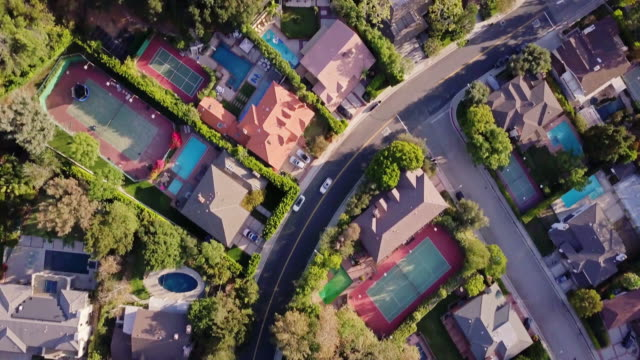 Top Down Shot of Affluent Residential Street Top down drone shot of a residential street in Deep Canyon, Beverly Hills, lined with large single family homes, many with backyard swimming pools or tennis courts. wealth stock videos & royalty-free footage
