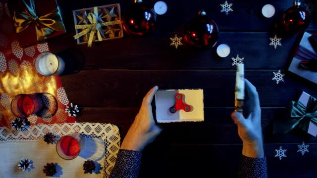 トップダウンのスピナーの中でクリスマスのプレゼント ボックスを開いて男性の手のショット ビデオ