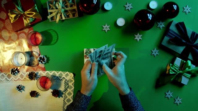 トップダウンの現金お金を数えるとクロマ キーを持つテーブルで新年のギフト ボックスに入れて男のショット ビデオ