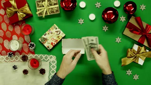 トップダウンの現金お金を数えるとクロマ キーを持つテーブルのクリスマス ギフト ボックスに入れて男のショット ビデオ