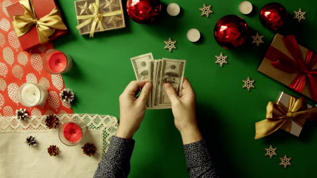 上下にクロマキーでクリスマス テーブルで現金を数える男のショット ビデオ